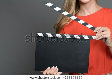 Close up a blond woman with her face not shown holding a movie clapperboard.