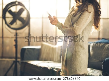 Close-up a brunette woman in comfortable clothing standing in a loft living room, holding her phone, arms crossed. Upper body shot, no face. Hair detail, and urban loft decoration. - stock photo