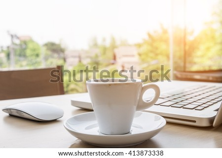 Close-up a cup of coffee on office desk at morning with laptop