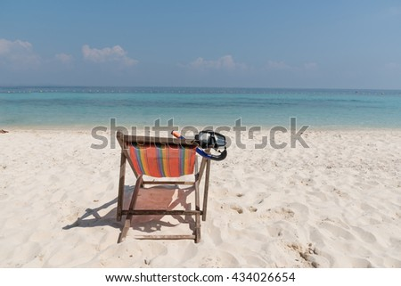 close up a diving mask hanging in a bright colored wooden beach chair on island tropical beach