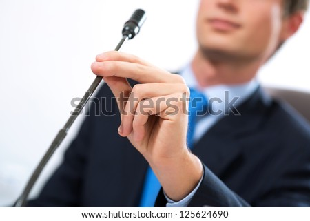 close-up a hand holding a microphone, chat at the conference - stock photo