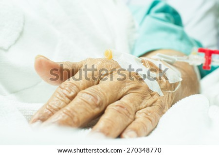 Close up a hand of an old woman patient in hospital with saline intravenous - stock photo