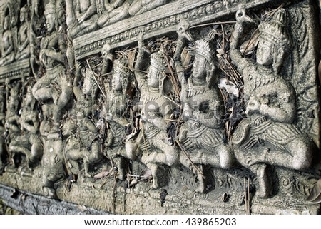 Close up Abandoned Stone Wall Carving Of religious legend in buddha temple at southeast asia with vintage filter background