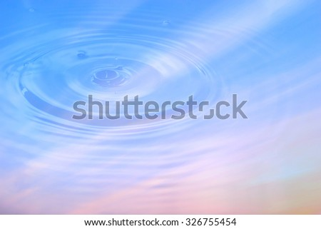Close up, abstract composition with water drops on water reflection of Sky gradient from blue to orange sunset.  - stock photo