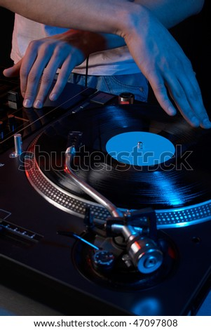 Close up acoustic vinyl player with dj hand