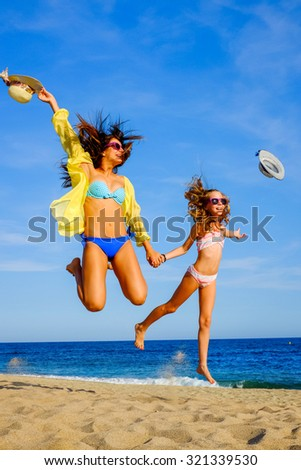 Close up action portrait of Young girls in swimwear jumping on beach. Two attractive happy women in bikini and sunglasses throwing hats in air.