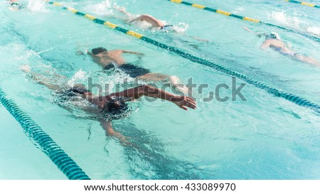 Close-up action shot of teen boy swimming front crawl stroke style in the blue water outdoor race pool. Focus on arm and water splash, some motion blurs. Swimming race and competition concept.Panorama