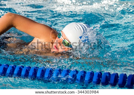 Close up action shot of young swim student at swimming practice.