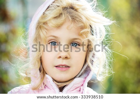Close up adorable little girl outdoors at beautiful autumn day