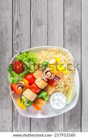 Close up Aerial Shot of Appetizing Kebabs on Flavored Yellow Rice with Veggies and Mustard Sauce, Served on Wooden Table with Copy Space. - stock photo