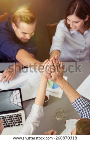 Close up Aerial View of Group of Friends Holding Hands Together at the Center While Having a Meeting at the Table. - stock photo