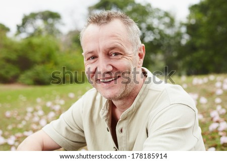 Close up age man portrait in the park - stock photo