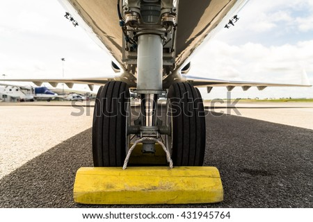 Close up aircraft nose landing gear on the tarmac with chock at the tire - stock photo