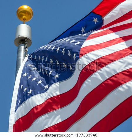 Close-up American flag blows in the wind with flag pole, focus on star of waving flag - stock photo