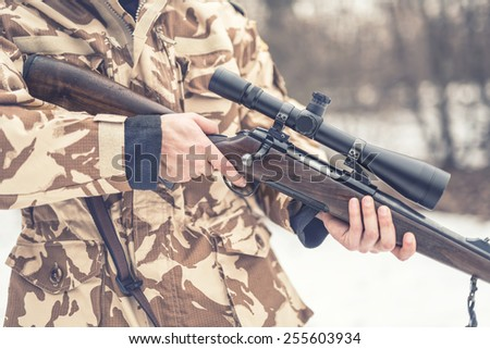 Close up and details of a man wearing a camouflage suit holding a sniper, rifle or gun - stock photo
