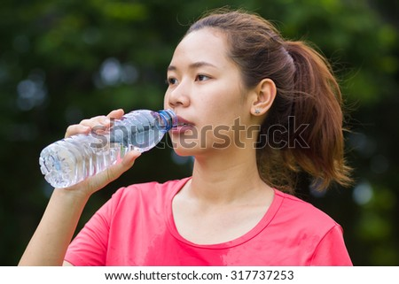 close up and selective focus of asian sporty woman try to take a bottle of water for drinking after exercising for freshness:woman relax and rest  after workouts at the park.woman fitness concept