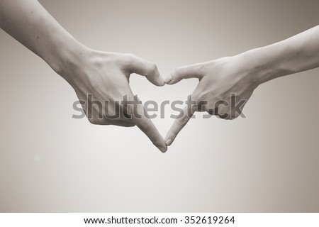 close up and selective focus on man and woman hands make heart shape over blurred beige sepia colored vintage tone background:abstract relationship of lovers concept.passion in love conceptual.better - stock photo