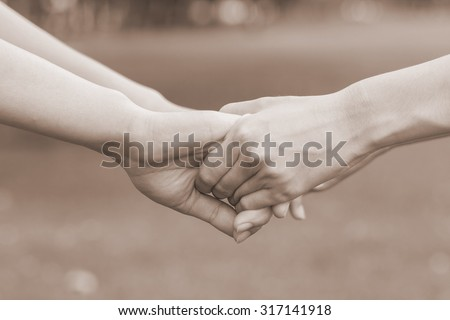 close up and selective focused of women hands holding together for helping and cheer up:supporting hand concept:family and friends concept.image in sepia vintage tone color.happy family.love and care - stock photo