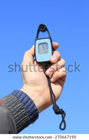 close-up anemometer in hand on blue sky background - stock photo