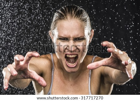 Close up Angry Female Fighter Reaching her Hands Towards the Camera While Screaming Out Loud Against Black Background with Water Drops. - stock photo