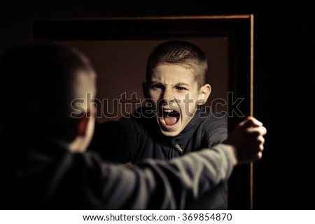 Close up Angry Young Boy Shouting on his Own Mirror Reflection with Mouth Wide Open Against Black Background. - stock photo