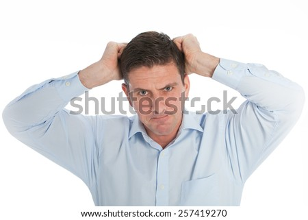 Close up Angry Young Businessman in Light Blue Shirt Pulling his Hair Out While looking at the Camera. Isolated on a White Background. - stock photo