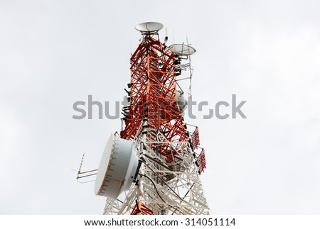 Close up antenna repeater tower on cloudy background. - stock photo