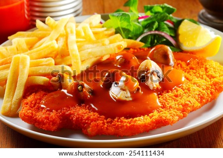 Close up Appetizing German Cuisine - Gourmet J��?���¤gerschnitzel with Sauce and Crispy Potato Fries on White Plate with Herbs and Lemon. - stock photo