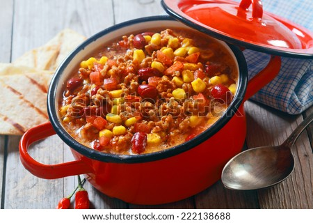 Close up Appetizing Healthy Meaty Dish on Red Pot with Serving Spoon on Side. Placed on Wooden Table. - stock photo