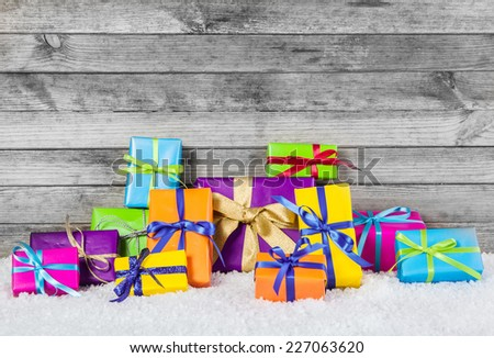 Close up Arranged Colored Christmas Gift Boxes with Ribbons on Man Made Snow with Gray Wooden Wall Background. - stock photo
