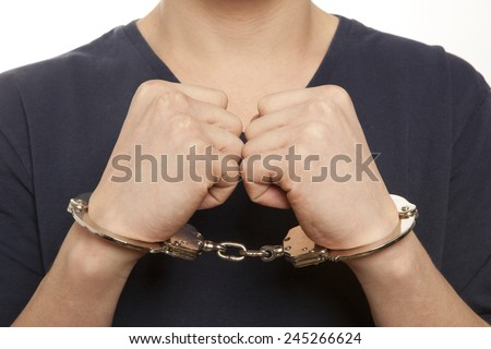 Close-up. Arrested man handcuffed hands at the back