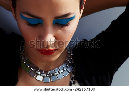 Close up artistic make-up  on female model against wall - stock photo