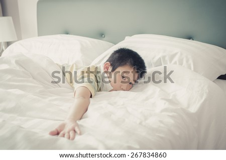 Close up Asain boy relaxing on bed. - stock photo