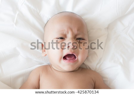 Close-up asian baby crying in bed - stock photo