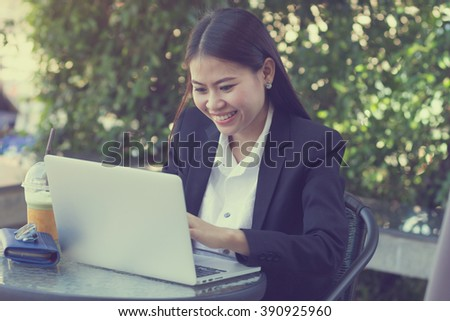 close up asian businesswoman searching on laptop at outside office:girl checking/update email or appointment:business concept.vintage tone filter effect.