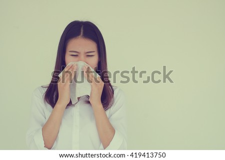 close up asian woman got a cold:young girl holding tissue in hand for reaction sneezing :healthcare concept.runny nose:sore or scratchy throat:risk of life:severe allergies:vintage tone filter effect - stock photo
