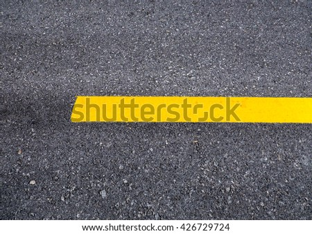 Close up asphalt surface of road divide yellow lines