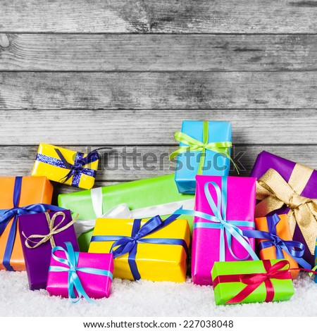 Close up Assorted Colored Christmas Gift Boxes with Ribbons on Snow with Wooden Wall Background. - stock photo