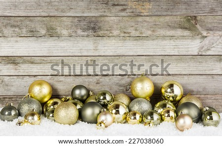 Close up Assorted Metallic Christmas Baubles For Decorations on the Snow with Wooden Wall Background. - stock photo