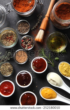 Close up Assorted Seed Type Spices and Sauces on Containers Placed on Top of the slate Table - stock photo