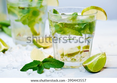 Close up at cold fresh lemonade drink with slice of lime on the glass. Slices of lime and mint leaves on a  white wooden background. Another glass in back.