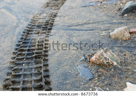 close-up at trial motorcycle tire's track in sand - stock photo