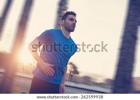 Close-up athlete running in the park along trees at sunset (strong motion blur, intentional sun glare and vintage color) - stock photo