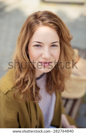 Close up Attractive Blond Teen Girl Sitting at the Bench, Looking at the Camera with a Smile.