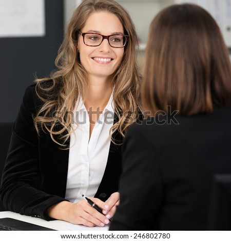 Close up Attractive Businesswoman with Long Blond Hair Talking to her Co-worker at her Worktable at the Office. - stock photo