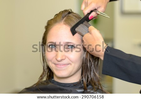 Close up Attractive Girl Inside a Salon, Smiling at the Camera While a Hairdresser is Fixing her Hair. - stock photo
