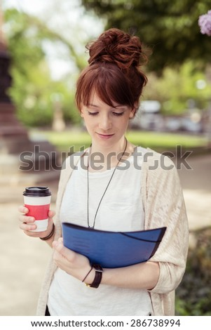 Close up Attractive Girl Student Holding a Cup of Coffee While Reading Something on Top of the File Folder on her Other Hand. - stock photo