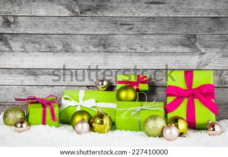Close up Attractive Green and Silver Christmas Decoration Items with Balls and Gift Boxes. Placed on Man Made Snow with Wooden Gray Wall Background. - stock photo