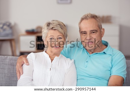 Close up Attractive Middle Aged Couple Sitting on the Couch Inside the House, Looking at the Camera - stock photo