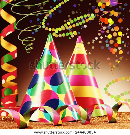 Close up Attractive Party Hats and Paper Streamers Placed on Platform, with Golden Granules, with Abstract Brown Background. - stock photo